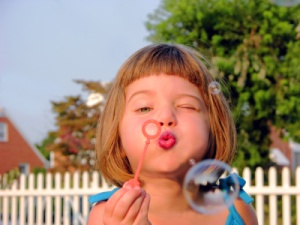 photo of child blowing bubbles